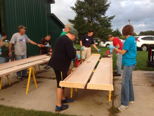 The Pew Crew works on pews for Lansing Catholic High School's new chapel.