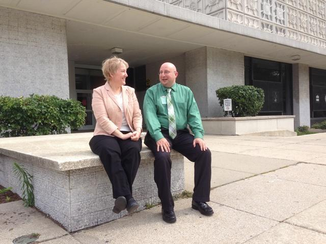 Public services librarian Anne Rau and library assistant Mark Buzzitta sit outside the entrance.