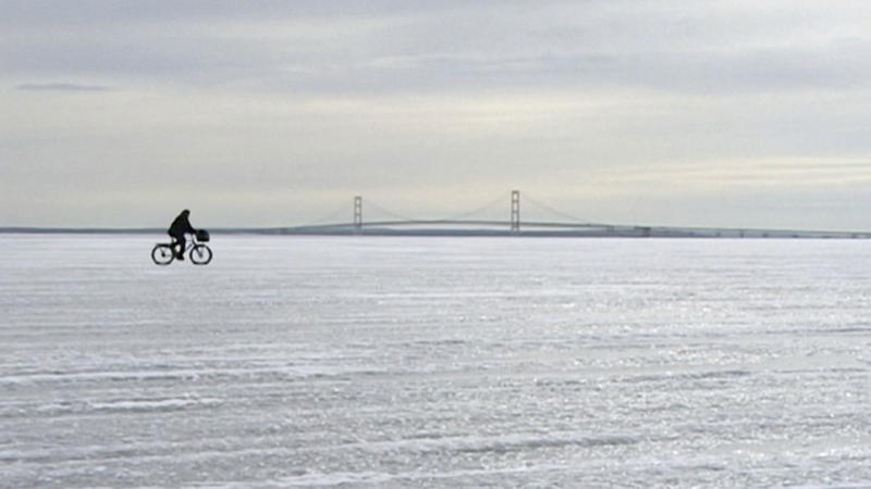 Bicyclist crossing over ice with Mackinac Bridge in background