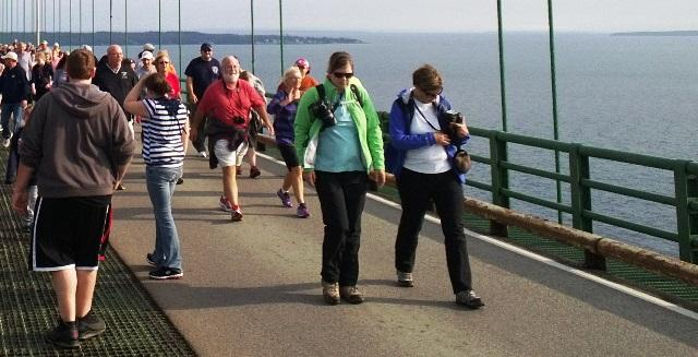 The Upper Peninsula and part of Mackinac Island can be seen behind these walkers on the bridge.