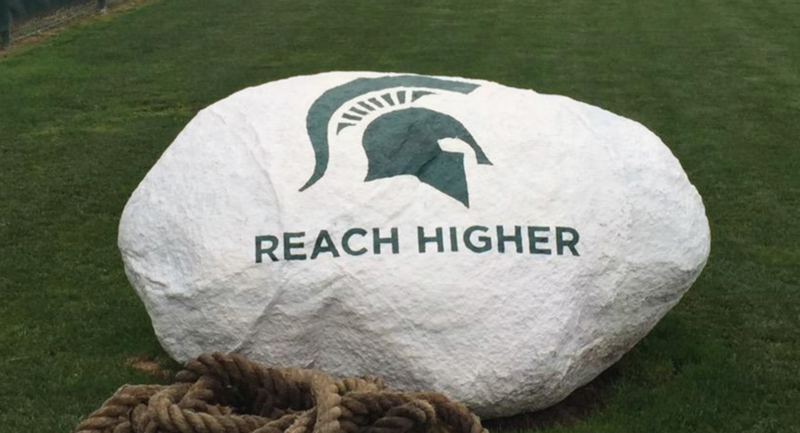 "MSU's 2015-16 motto ""Reach Higher"" displayed on the practice field."