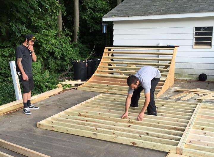 two men building skateboard ramp