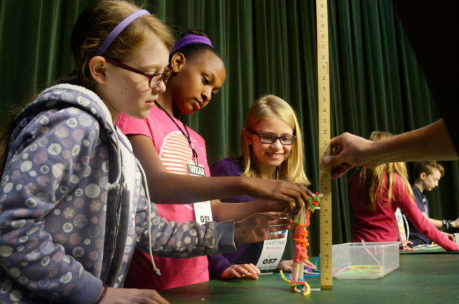 "Dominique Pruitt-Wright (center) and team attempt to build a structure for the ""Curious Crew"" engineering challenge."