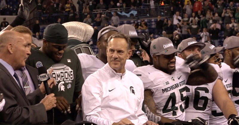 Mark Dantonio and the MSU football celebrate at Lucas Oil Stadium after winning the Big Ten Championship over Iowa.