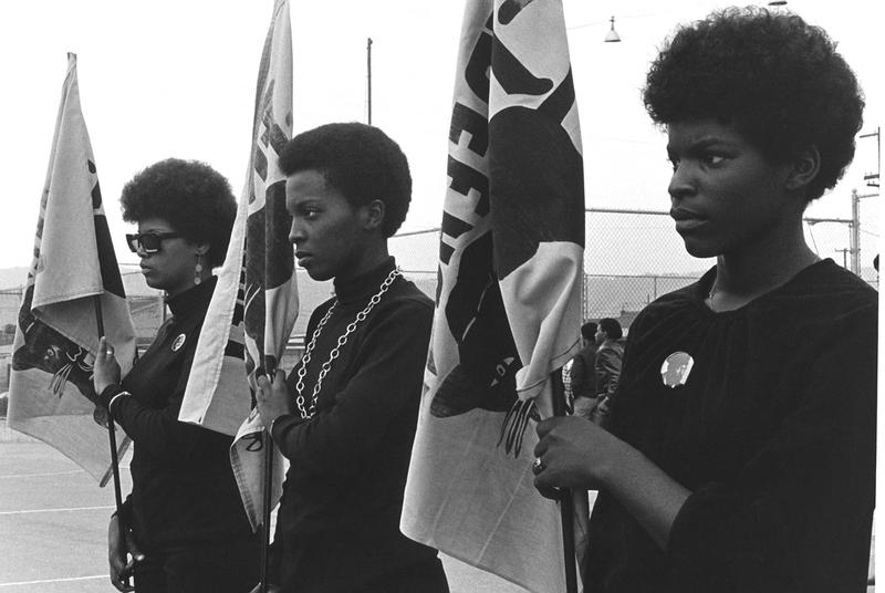 Women drilling with Panther flags.