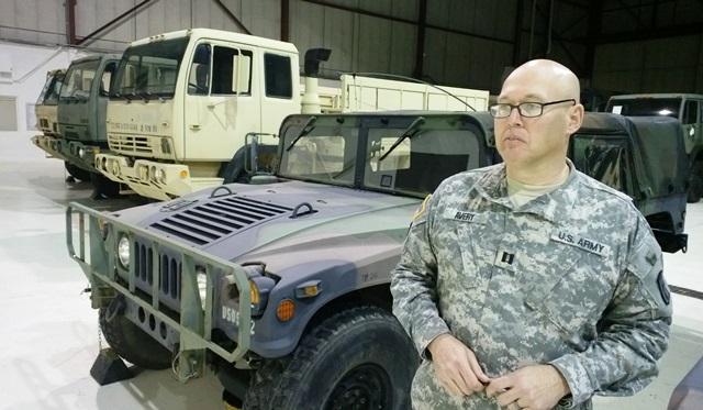 man in camo gear stands near jeep