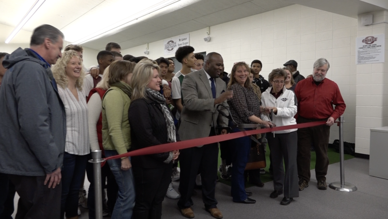 Okemos athletic director Ira Childress cuts the ribbon during the grand opening of the Okemos High School strength and conditioning center.