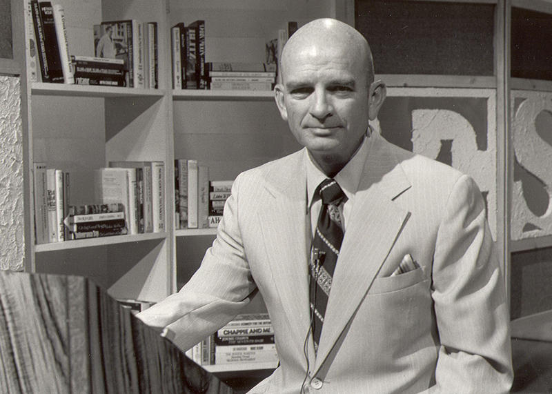 Dick Estell on TV set with bookshelves