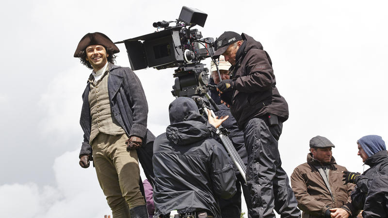 Aidan Turner, in costume as Ross Poldark, stands by the camera.