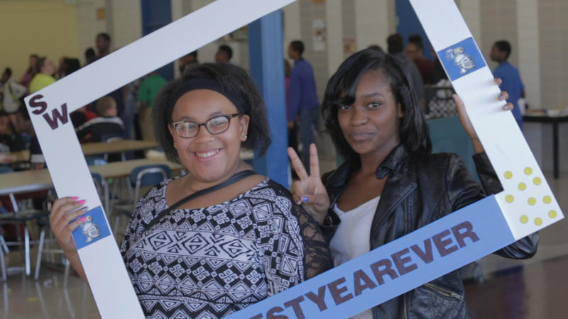 Two female students smiling at a Flint school event