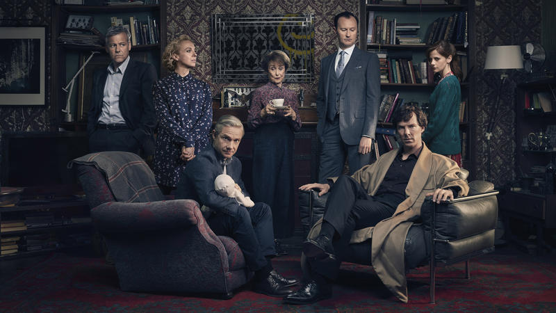 Sherlock Holmes cast in front of fireplace