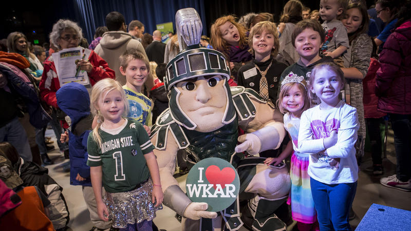 "Sparty with kids holding ""I heart WKAR"" sign"