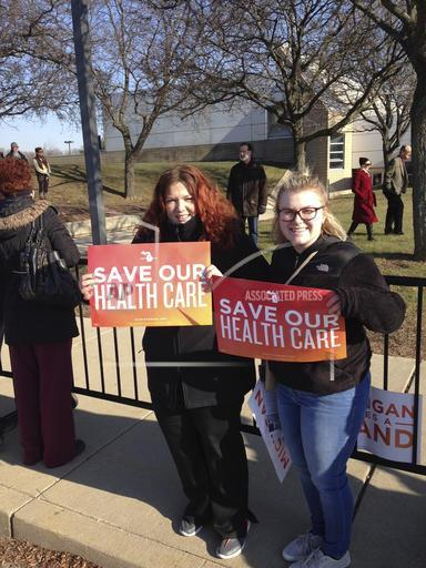 Britt Waligorski, 31, and Mary Whitfield, 18, attend an Affordable Health Act rally on Sunday, Jan. 15, 2016, in Warren, Mich. Thousands of people showed up in freezing temperatures on Sunday in Michigan where Sen. Bernie Sanders called on Americans to re