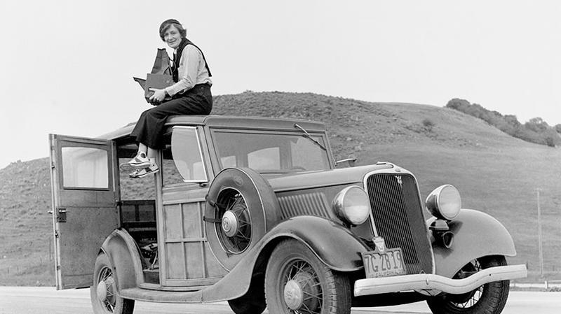 Dorothea Lange sitting on car