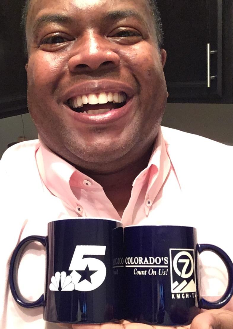 WKAR Digital News Director Reginald Hardwick holds TWO mugs. They represent the first and last tv stations he worked at before joining the WKAR family. He hopes to earn a WKAR mug soon.