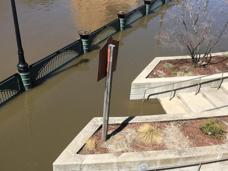 The swollen Grand River flooded the riverwalk next to the Lansing Center on April 8, 2017.