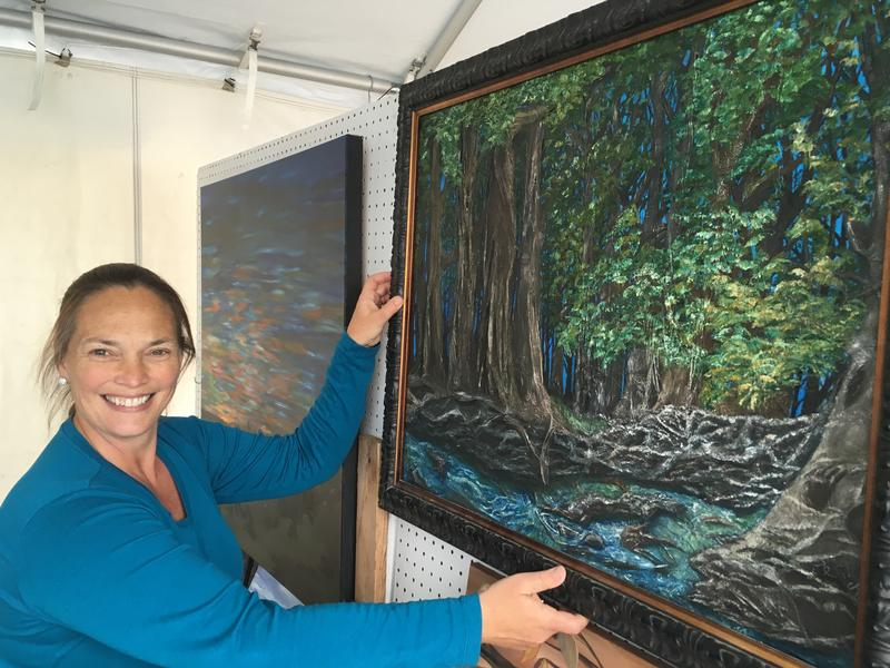 Painter Jennifer Hahn prepares her painting for the East Lansing Arts Festival. This is her first time displaying art at the festival.