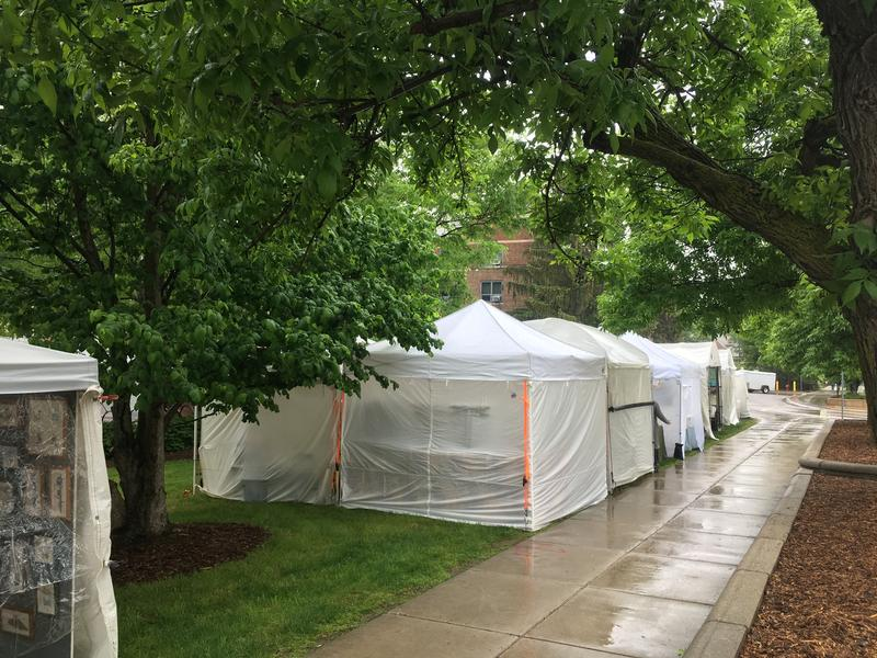 Tents line Michigan Avenue with artists and artwork inside during rainstorm.