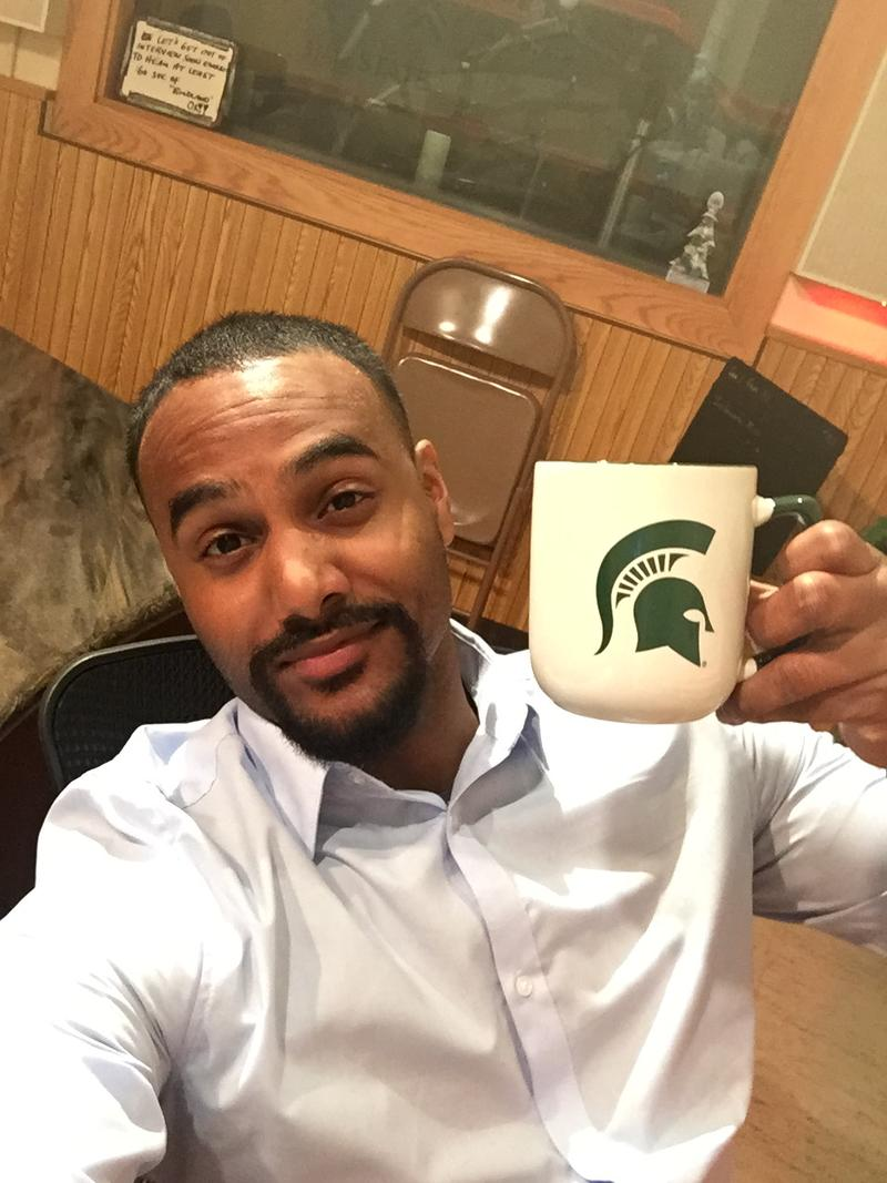 "WKAR's Al Martin: ""I've attached a selfie of myself posing with my favorite coffee mug. The reason this is my favorite mug is because it represents the pride that I have in my alma mater of Michigan State University."""