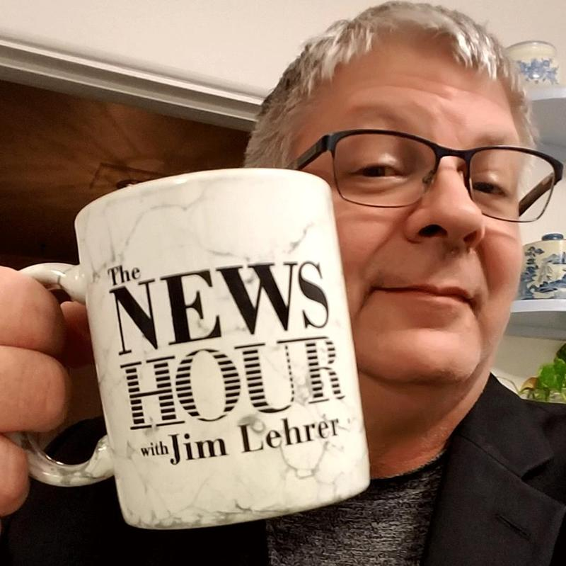 "Bill Richards, manager on the communications team for WKAR Public Media and the College of Communication Arts and Sciences holds up a mug that should be familiar to longtime fans of the ""News Hour"" on PBS."