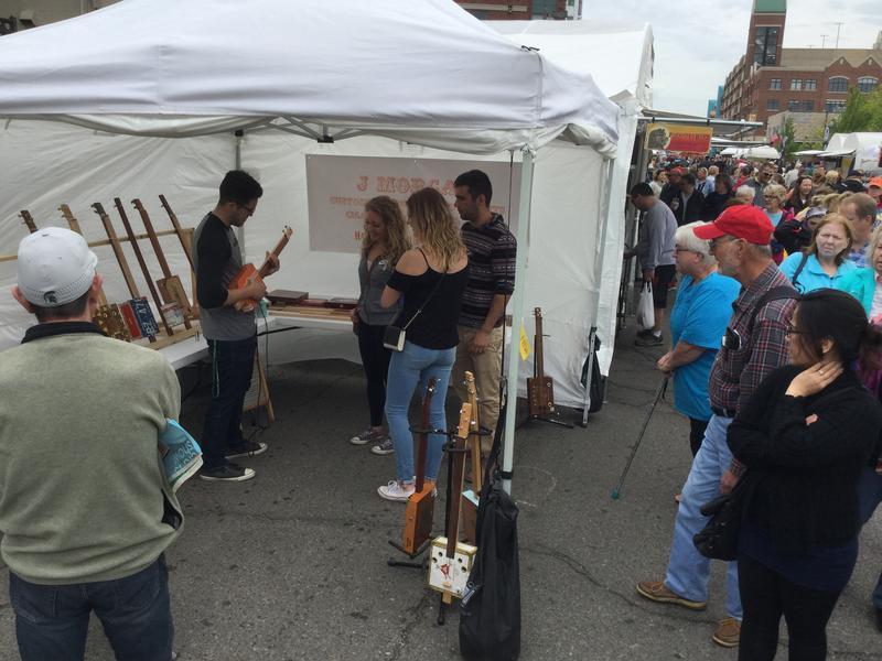 Exhibit featuring cigar box guitars draws spectators at East Lansing Art Festival.