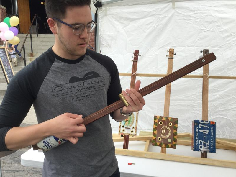 Man plays diddley bow at East Lansing Art Festival.