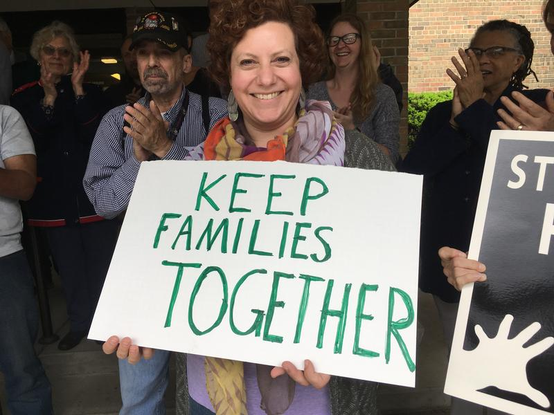 Member of All Saints Episcopal Church holds up sign in support of immigrants.