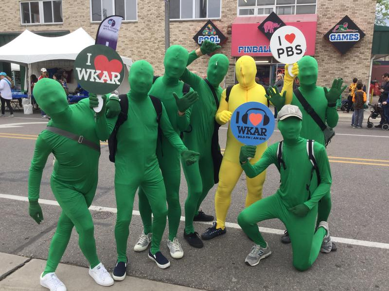 The green guys (and one yellow guy) hold up WKAR signs at the East Lansing Art Festival.