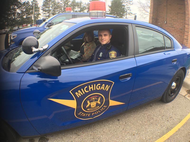 WKAR's Brooke Allen and Michigan State Patrol Trooper B.J. Breslin in a patrol car.
