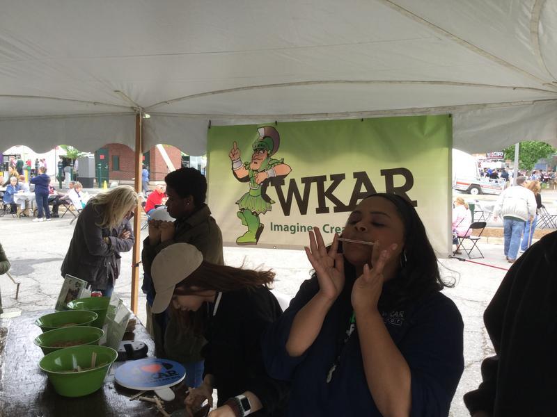 WKAR's Shadonna Crosby plays a handmade kazoo at the WKAR Kids Booth at the East Lansing Art Festival.