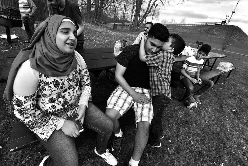 Yasser Jasem, 5, tells big brother Hussain, 18, a secret as sister Rokaia, 12, left, and other family and friends gather for a picnic at Hawk Island in Lansing.