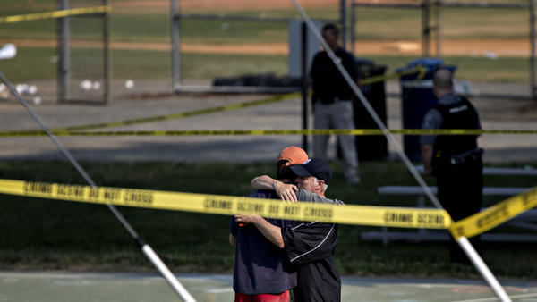 Two people hug in an area blocked off by police crime scene tape in Alexandria, Va., after a shooting during a congressional baseball practice Wednesday.