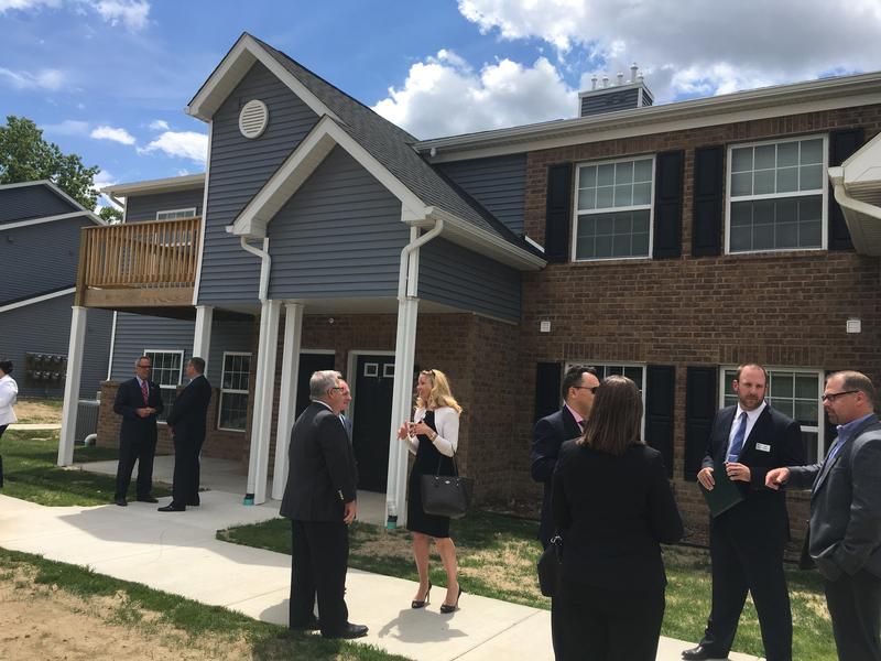 Community leaders talk after the ribbon cutting of Prestwick Village Apartments in Holt.
