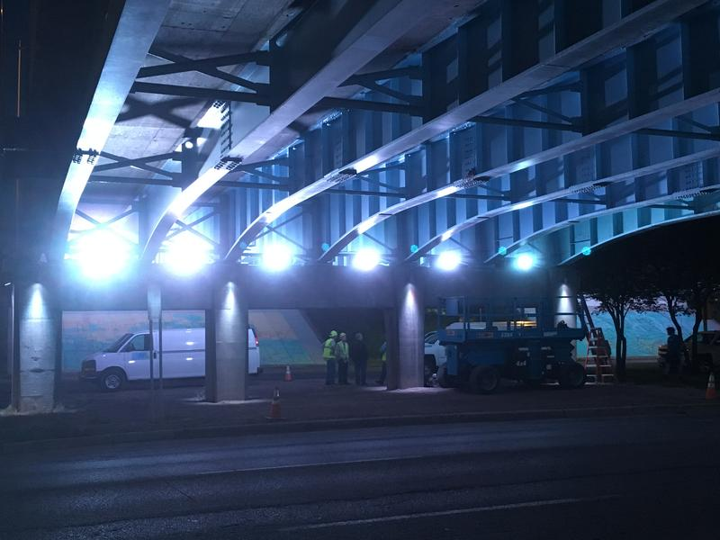 Bright lights shine along Michigan Ave. under US 127 overpass.