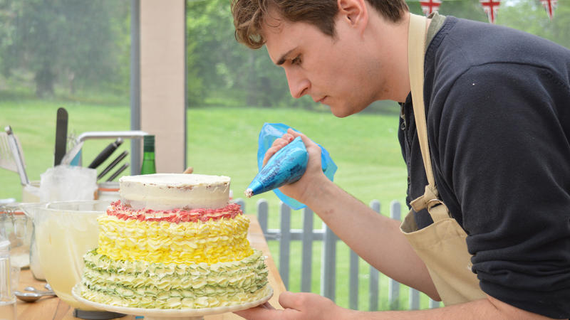 Tom piping the top of his cake.