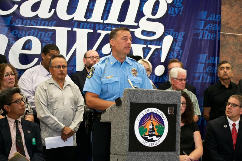 Lansing PD Chief Mike Yankowski (center at the podium) address the media surrounded by members of the Hispanic community. Mayor Virg Bernero (sitting on far right) addressed the attack of an immigrant.