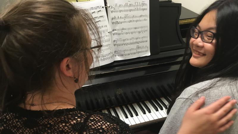 Mentor Cwen Homa (left) pats mentee Joey Tan (right) on the back during piano practice.