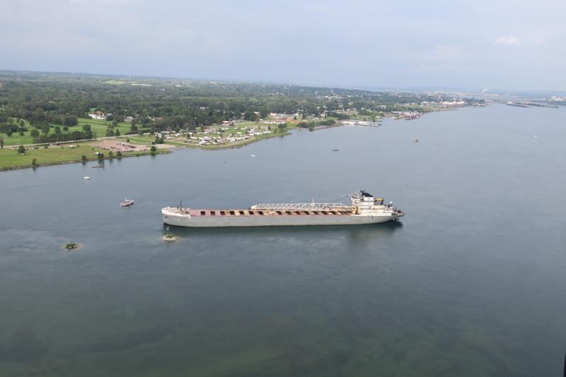 The 629-foot cargo vessel Calumet sits hard aground in the St. Mary's River southeast of Sault Ste. Marie, Michigan, while a Coast Guard response boat - medium encircles the vessel, August 10, 2017. The vessel was heading to its next port of call in Brevo