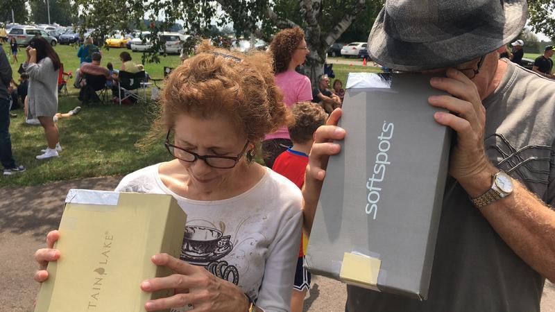 Rebecca Ammon (left) of East Lansing looks inside homemade solar eclipse kit.