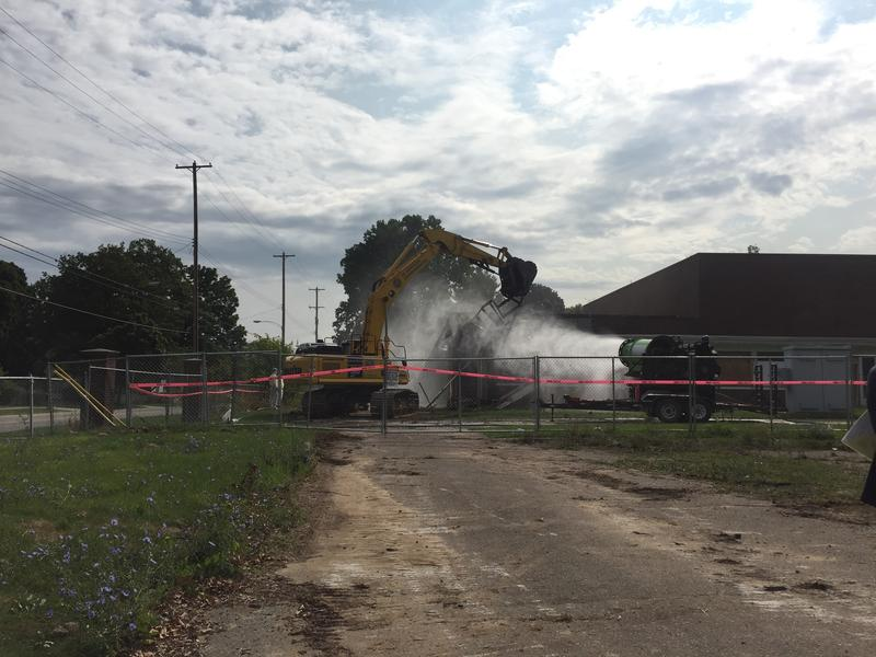 Heavy equipment tears down an auditorium so crews cand build new apartments.