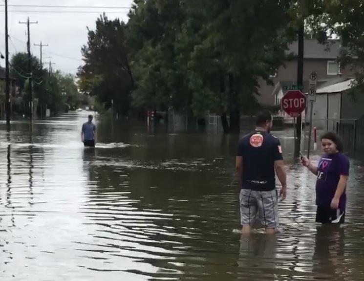 People standing in knee-high water in Houston.