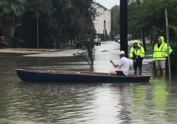 A man in a canoe in the streets of Houston.