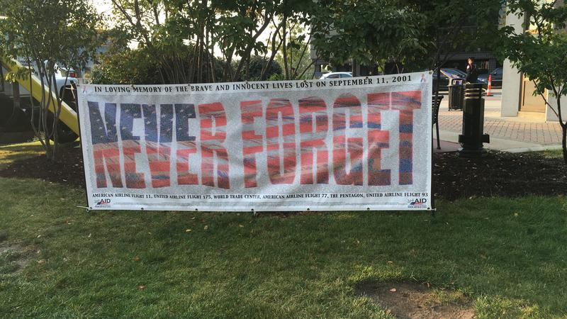 """Never forget"" banner is posted at 9/11 ceremony in Lansing on Sept. 11, 2017."