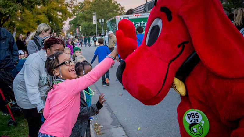 Clifford high-fiving a child on the street