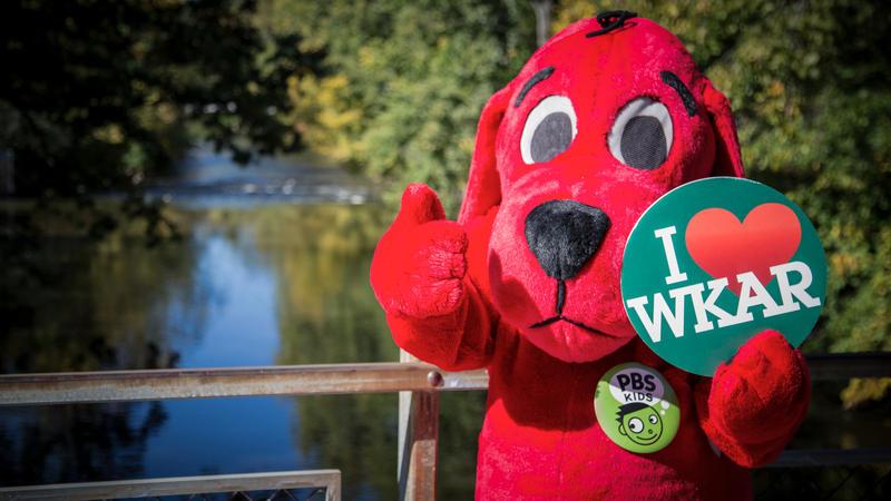 Clifford on the red cedar river bridge holding I heart WKAR button