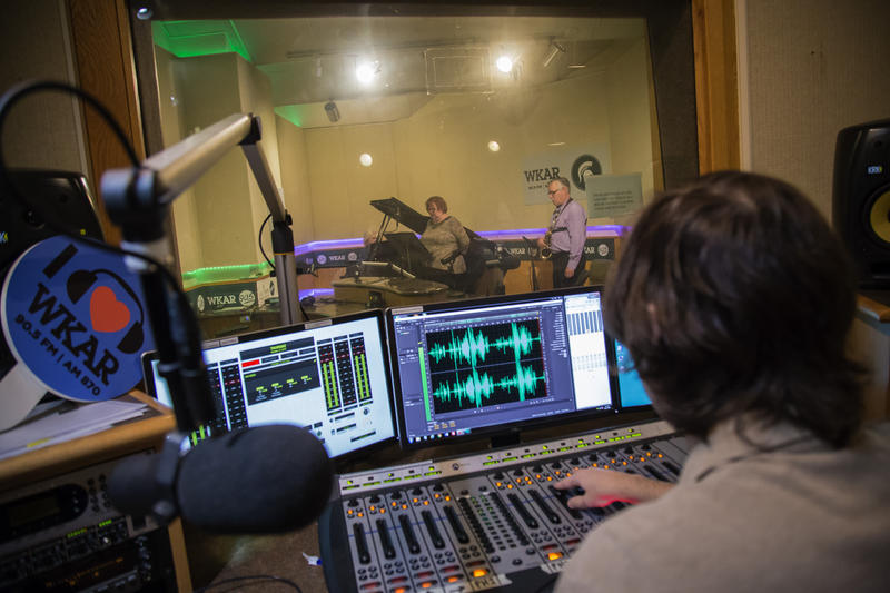 Deborah Moriarty (piano); Melanie Helton (soprano); and James Forger (saxophone) as engineer Drew Hill monitors levels from the WKAR booth