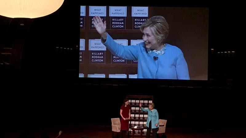 Former presidential candidate and Secretary of State Hillary Clinton (right in the blue) waves to crowds after speaking in Ann Arbor on October 24, 2017.