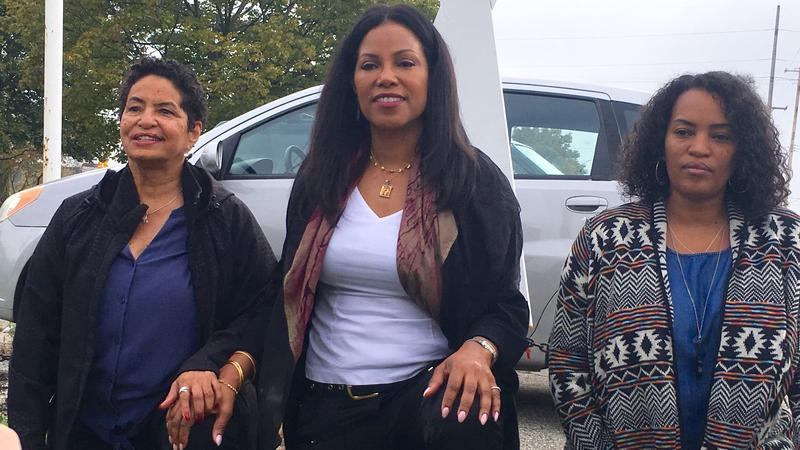 "Ilyasah Shabazz (center) kneels in front of a makeshift ""X"" cross bearing the name of her grandfather, the Rev. Earl Little.  Also pictured is Shabazz's cousin, Deborah Jones (left) and Jones' daughter Shahara Brown."