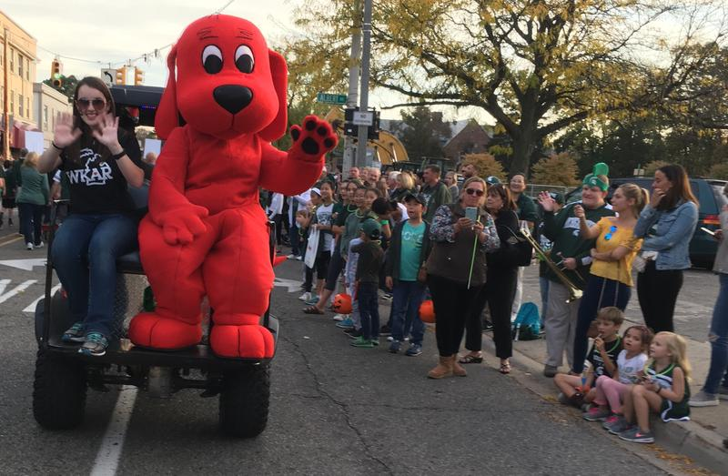 Clifford the big red dog waves at children.
