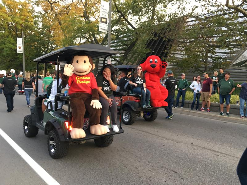 Curious George and Clifford wave to children as part of the WKAR entry.